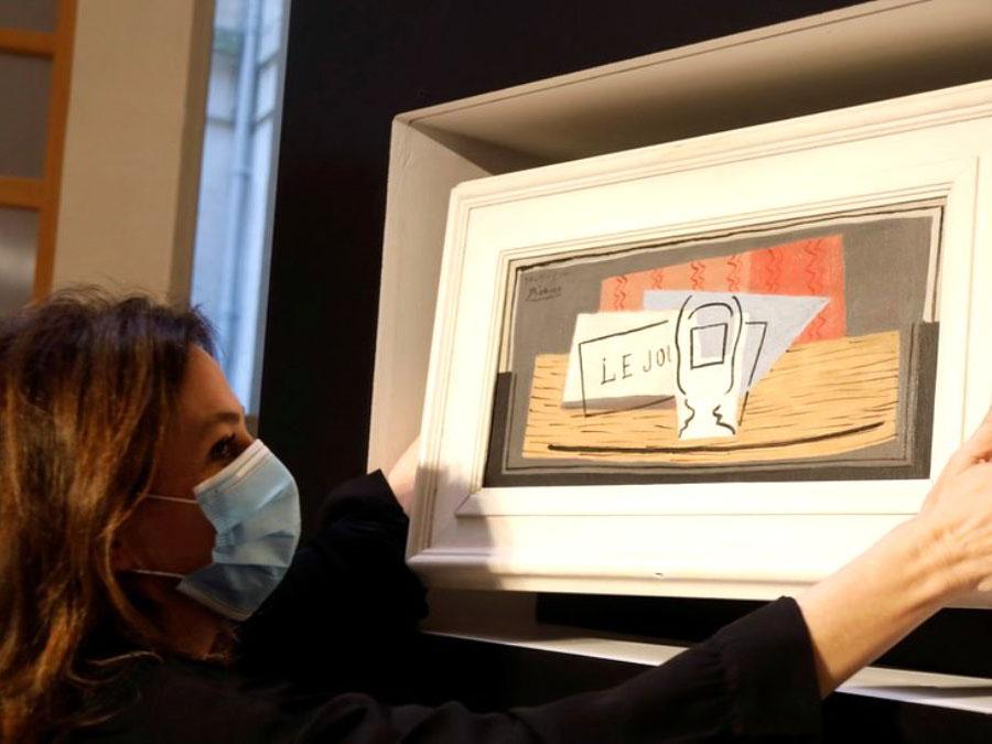 Женщина в маске и с картиной в руках