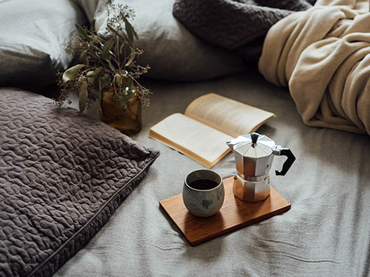 Чашка кофе на кровати с книгой